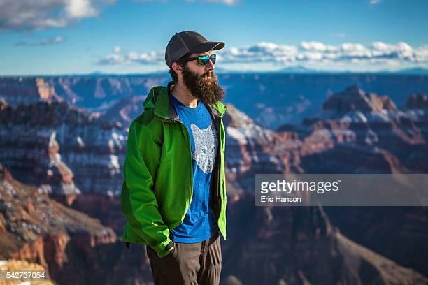 bearded man stands at the edge of the grand canyon - flanco de valle fotografías e imágenes de stock