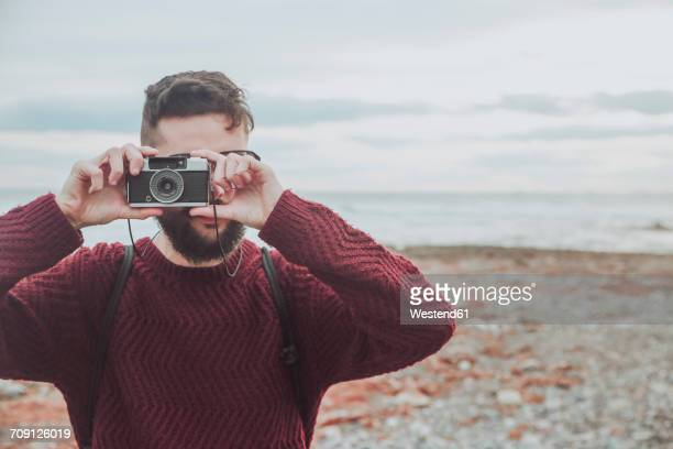 Bearded man taking photo on the beach with vintage camera