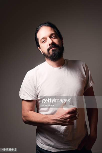 bearded man thinking over a cup of coffee - zwart haar stockfoto's en -beelden