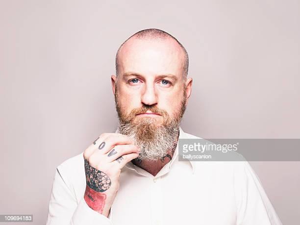 Bearded Man Touching Beard, Studio Portrait.