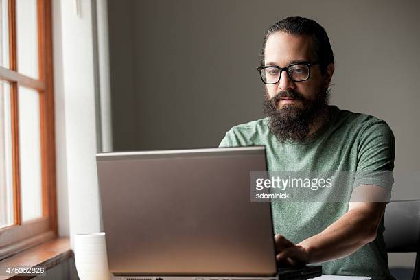 bearded man using laptop by window - horn rimmed glasses stock pictures, royalty-free photos & images