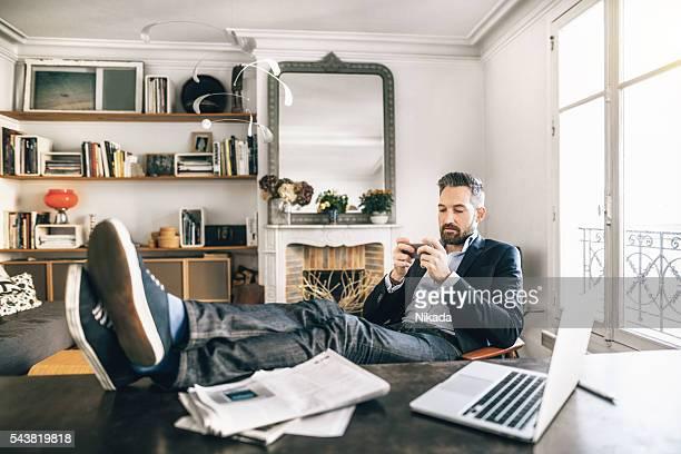 ひげを生やした男性 homeoffice スマートフォンを使用して