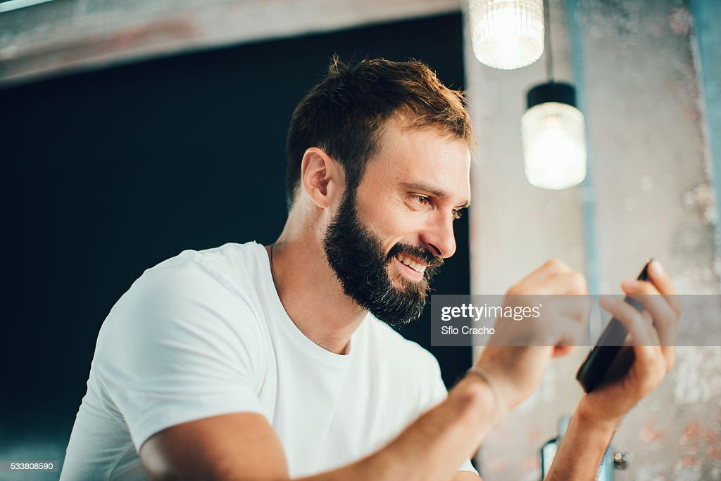 Bearded man using smartphone : Foto stock