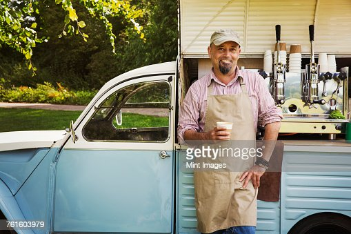 Bearded man wearing apron standing by blue mobile coffee shop, holding hot drink, smiling at camera.