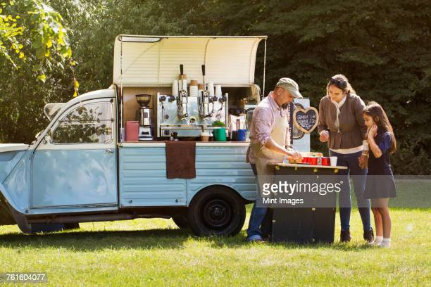 bearded man wearing apron, woman and girl standing by blue mobile coffee shop. - food truck ストックフォトと画像