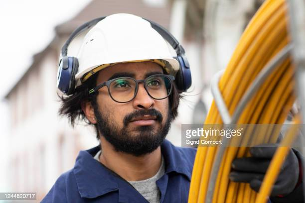 bearded man wearing eyeglasses and white hard hat working on construction site. - sigrid gombert stock pictures, royalty-free photos & images