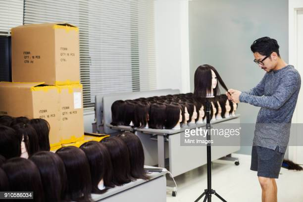 bearded man wearing glasses standing indoors, cutting hair of brown wig on mannequin head. - cabello largo fotografías e imágenes de stock
