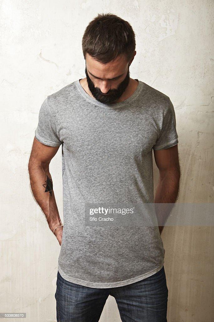 Bearded man wearing grey t-shirt against wall : Foto stock