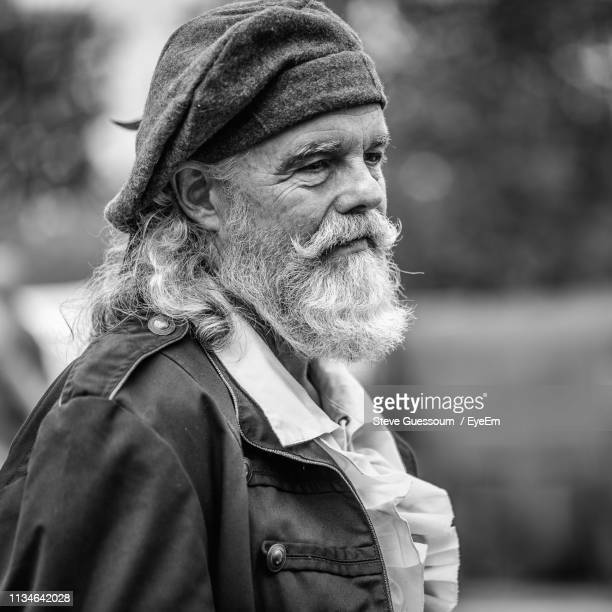 bearded man wearing hat outdoors - steve guessoum stockfoto's en -beelden