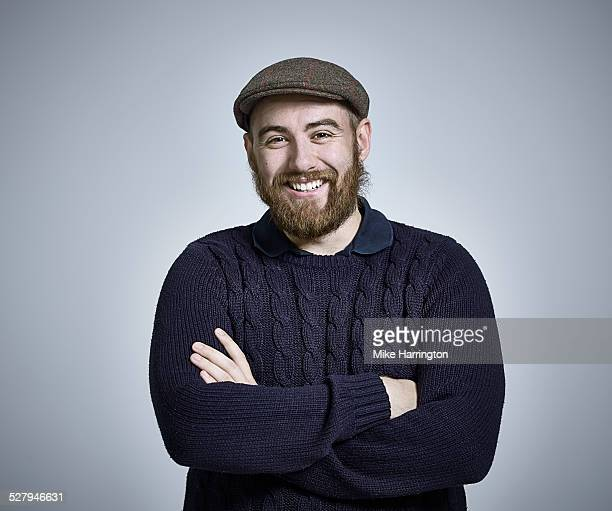Bearded Man wearing jumper and flat cap smiling