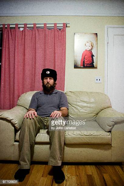 Bearded man wearing Russian hat sits on couch