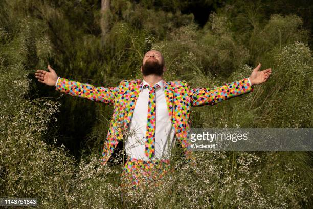 bearded man wearing suit with colourful polka-dots enjoying nature - multi colored suit stock photos and pictures