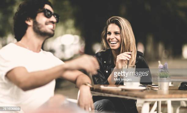 Bearded man wearing sunglasses and woman with long blond hair sitting outdoors at a table in a cafe, laughing.