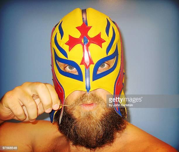 Bearded man wearing wrestling mask twirls mustache