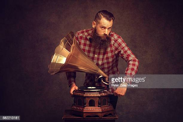 Bearded man winding up a gramophone