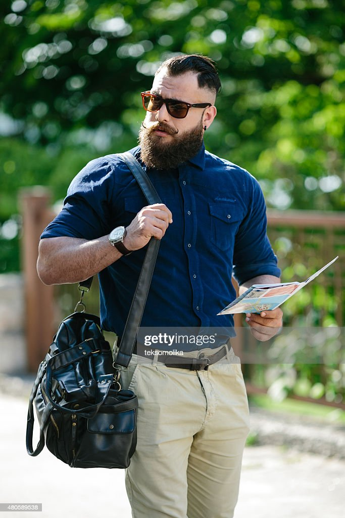 bearded man with a map in hand : Stock Photo