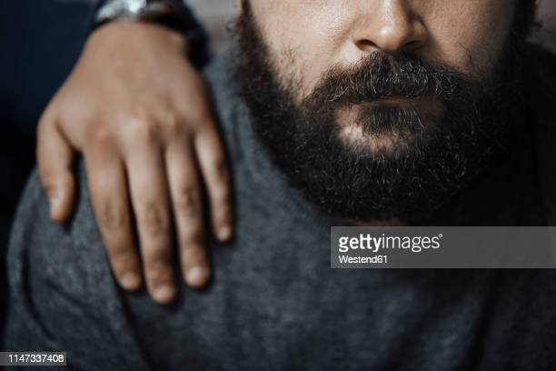 bearded man with boyfriend's hand on his shoulder, partial view - hand on shoulder stock pictures, royalty-free photos & images
