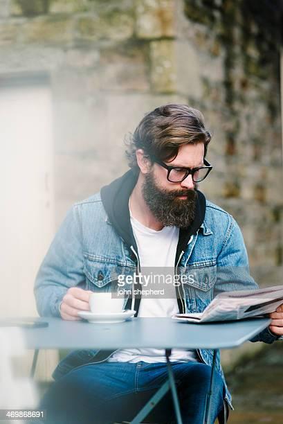 Homme barbu avec un café et le journal