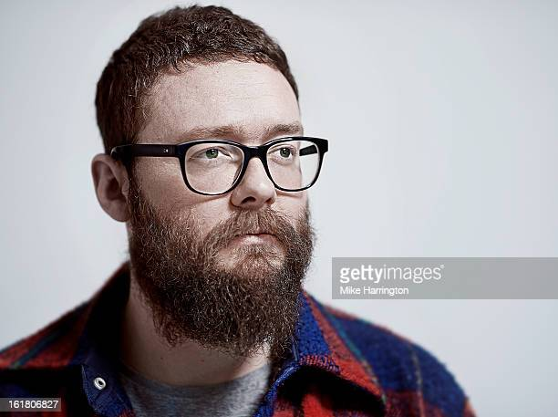 Bearded man with glasses looking to side of camera