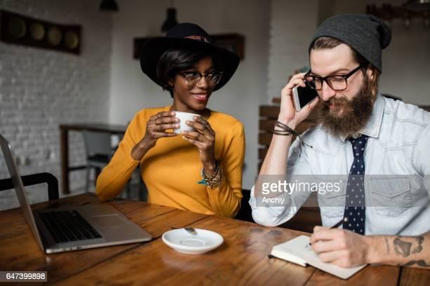 Homme barbu avec des lunettes, portant chapeau, parler au téléphone, partenaire de boire du café