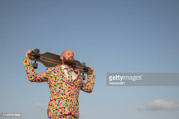 bearded man with longboard on his shoulders wearing suit with colourful polka-dots - estilo de vida ativo imagens e fotografias de stock