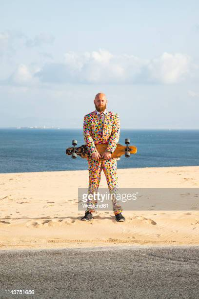 bearded man with longboard wearing suit with colourful polka-dots standing on sand dune - multi colored suit stock pictures, royalty-free photos & images