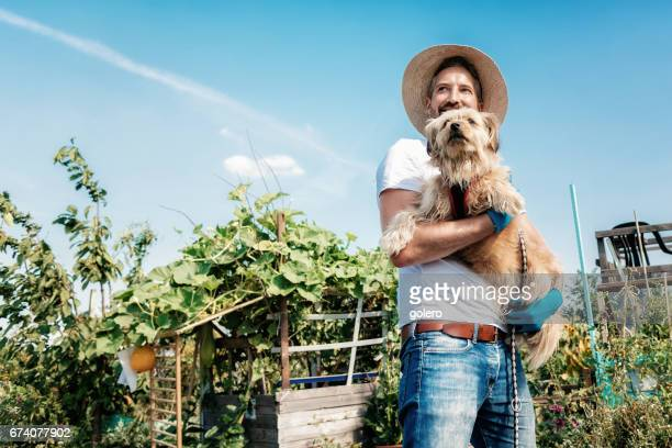 bearded man with straw hat holding dog in arm in garden