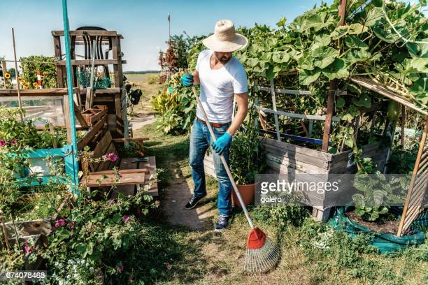 bearded man with straw hat working in city garden in Berlin