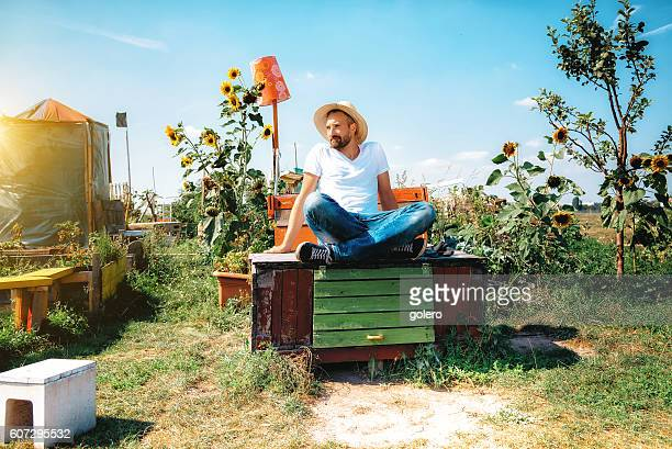bearded man with sun hat sitting in garden on box