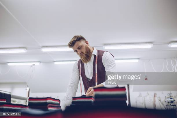 bearded man working with textile - customised stock photos and pictures