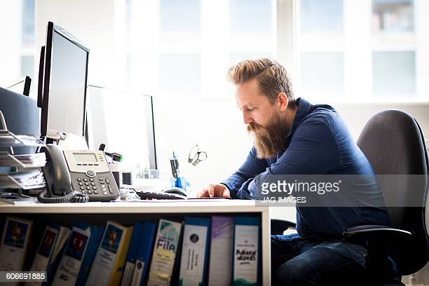 bearded man works at his desk