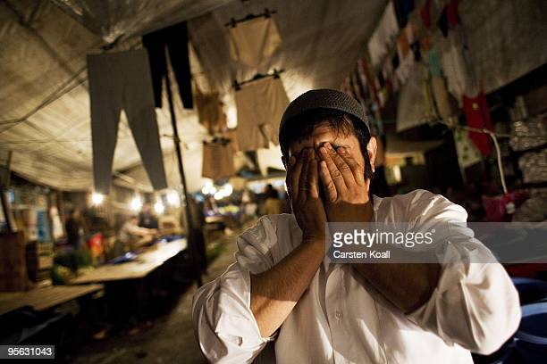 Bearded market seller holds his hands in front of the face during the weekly bazaar in the district Tarlabasi on May 14, 2006 in Istanbul, Turkey....