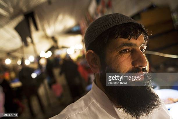 Bearded market seller smirks behind his stall during the weekly bazaar in the district Tarlabasi on May 14, 2006 in Istanbul, Turkey. Tarlabasõ is a...
