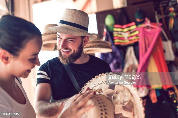 bearded market vendor offering hat to a lady - straw hat stock pictures, royalty-free photos & images