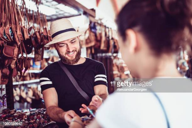 Bearded Market Vendor Offering Leather Bags To A Girl