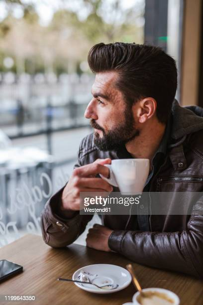 bearded mature man in a coffee shop looking out of window - レザージャケット ストックフォトと画像