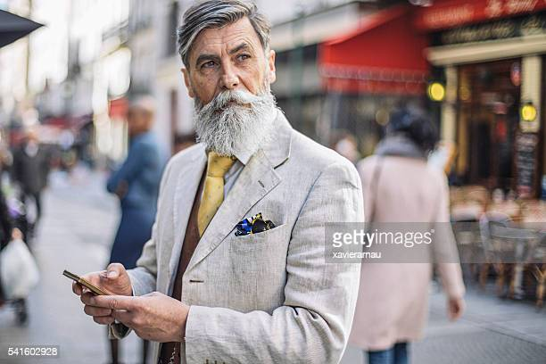 bearded mature man texting at the street - fashionable stock pictures, royalty-free photos & images