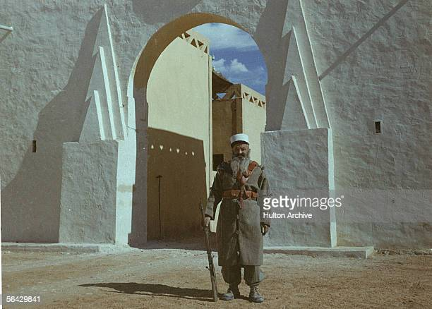 A bearded member of the Foreign Legion stands at attention before an archway at Legion headquarters Sidi Bel Abbes Algeria 1940s