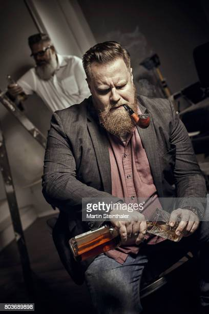 Bearded men with pipe drinking whiskey