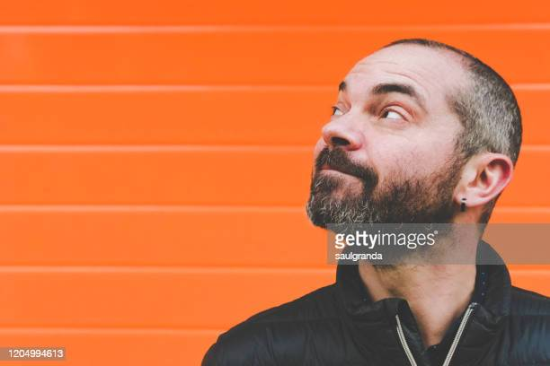 bearded mid adult man looking up - orange background stock pictures, royalty-free photos & images