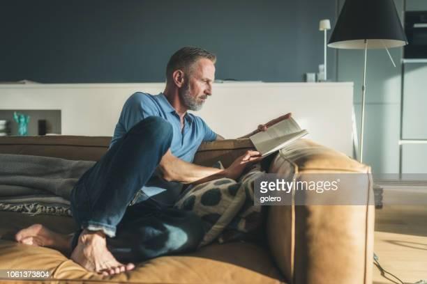 midaged bärtigen buch auf sofa - lesen stock-fotos und bilder