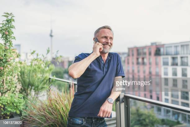 bearded midaged man talking on mobile at balcony in berlin - polo shirt stock pictures, royalty-free photos & images