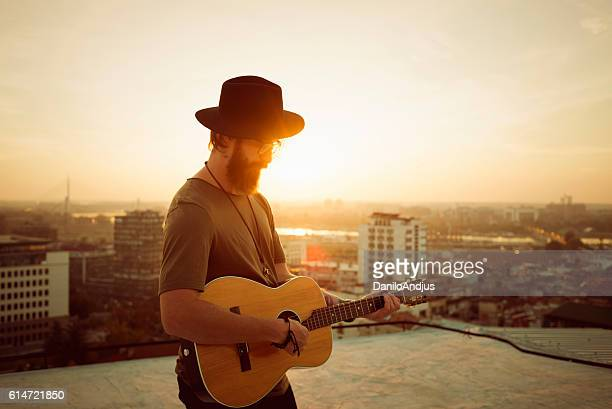 bearded musician playing the guitar on the roof - songwriter stock pictures, royalty-free photos & images