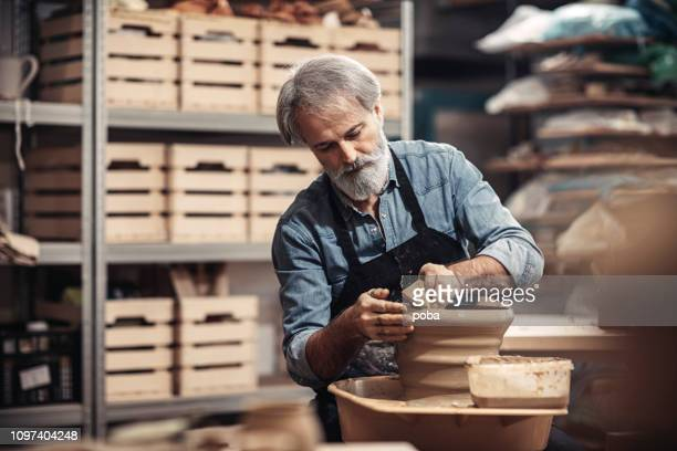 bearded old craftsman in pottery workshop - potter stock pictures, royalty-free photos & images
