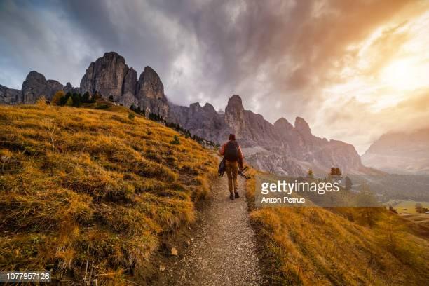 bearded photographer in dolomites mountains, passo gardena, italia. timelapse - dolomiti foto e immagini stock