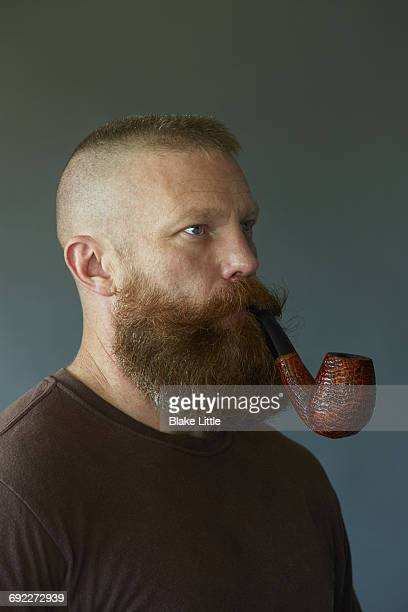 bearded pipe smoking man studio portrait - half shaved hairstyle stock pictures, royalty-free photos & images