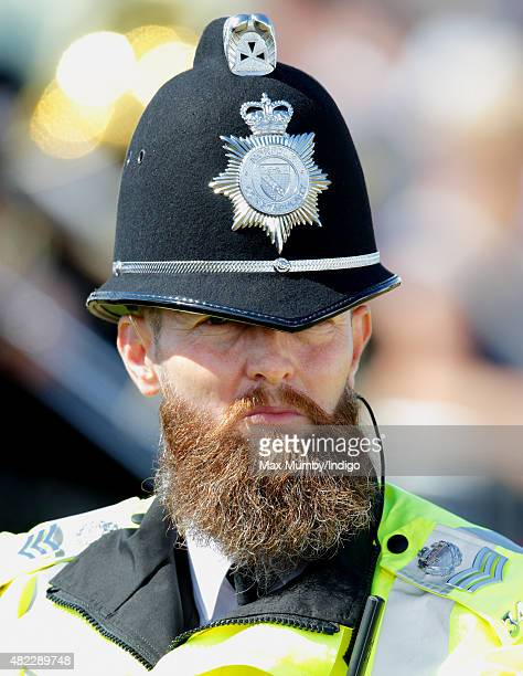 A bearded police officer awaits the arrival of Camilla Duchess of Cornwall and Prince Charles Prince of Wales for their visit to the Sandringham...