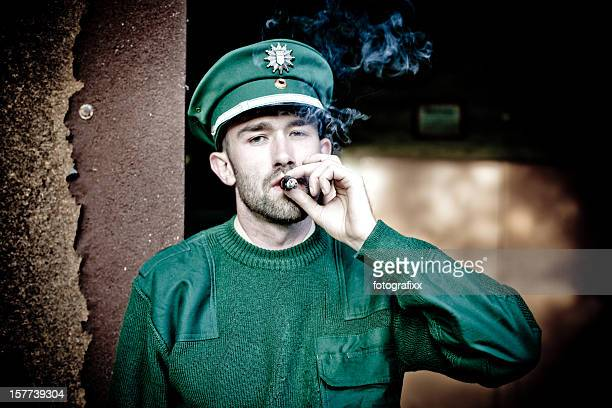 bearded policeman wears a green uniform and smokes a cigar