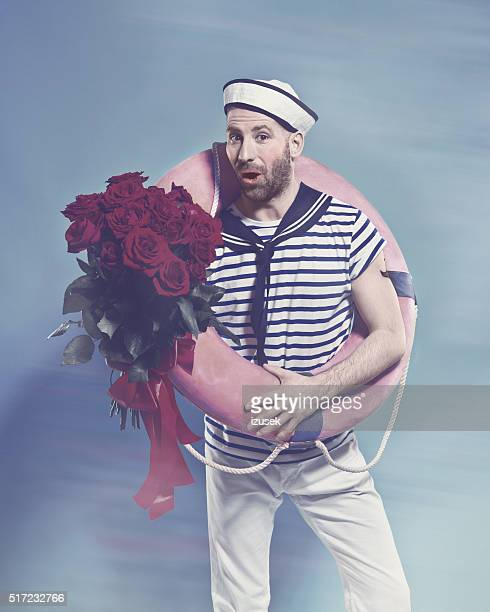 Bearded sailor holding lifebuoy and bunch of roses