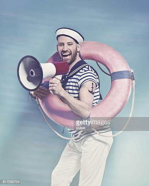 Bearded sailor holding lifebuoy, shouting into megaphone